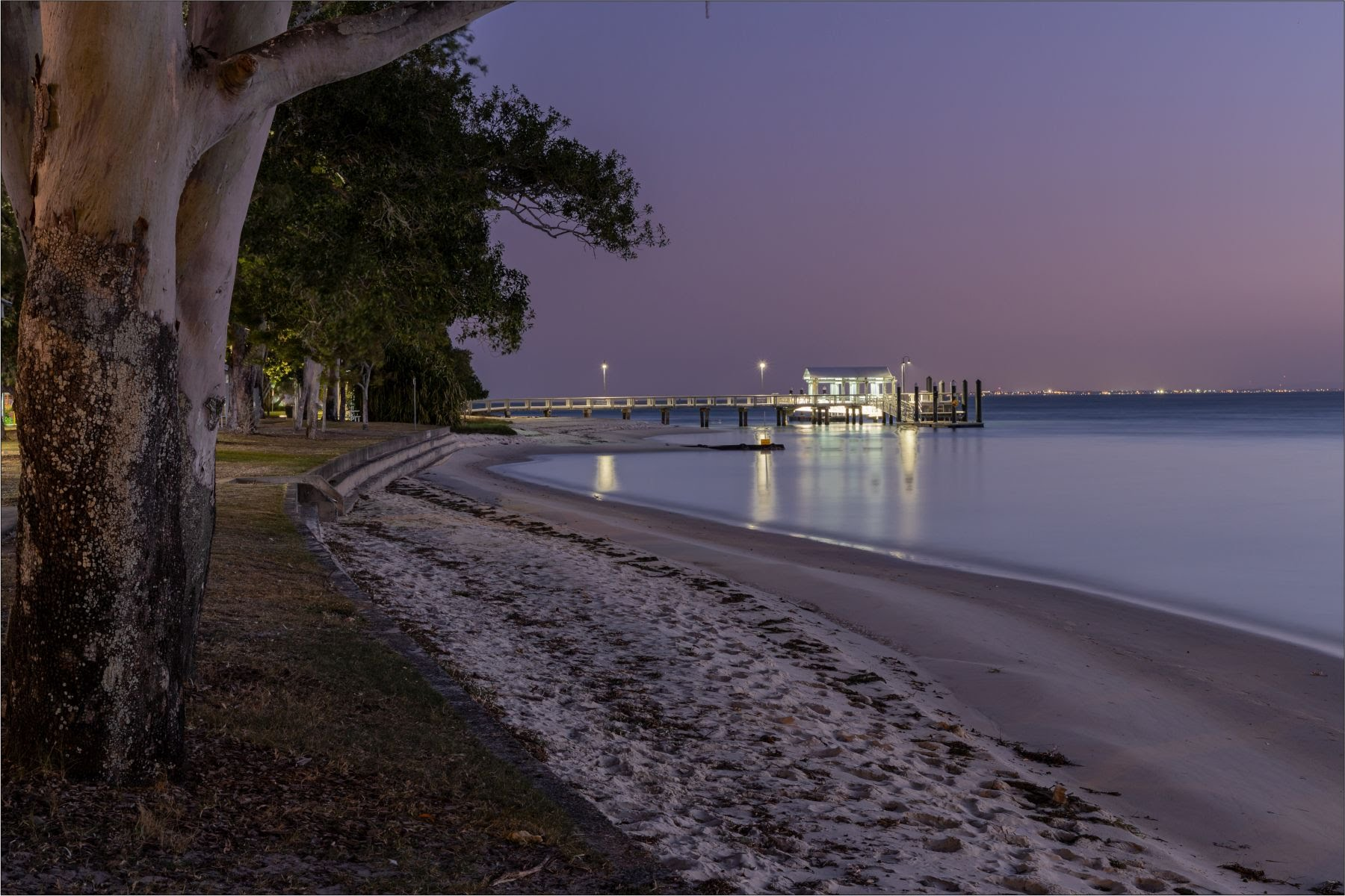 image at dusk of water and jetty from the side on shore